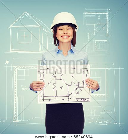 building, developing, consrtuction and architecture concept - smiling businesswoman in white helmet showing blueprint