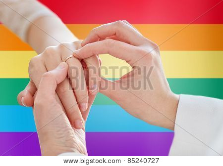 people, homosexuality, same-sex marriage and love concept - close up of happy lesbian couple hands putting on wedding ring over rainbow flag background