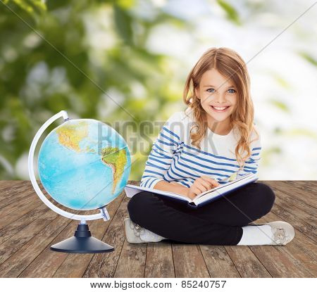 education, geography, childhood, people and school concept - little student girl studying with globe and book over green background