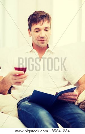 leisure, drinks, retirement, education and lifestyle concept - happy man with book and glass of rose wine at home