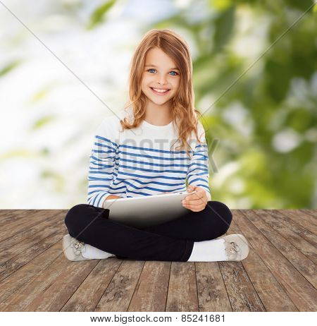 education, technology, childhood and people concept - happy little student girl with tablet pc over greed background