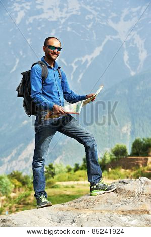 Indian male guide tourist travellerwith map in Himalayas mountains