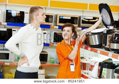 Young man choosing electric oven in home appliance shopping mall supermarket