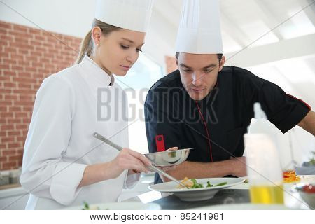 Girl in cooking training class with chef