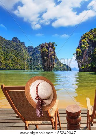 Exotic rest in Thailand. The coast of the gulf in the Andaman Sea. Convenient chaise lounge and an elegant hat on one