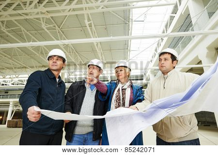 Architects and engineer workers with blueprints inside building under construction