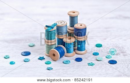 Collection Of Spools  Threads In Blue, Aqua Colors Arranged On A White Wooden Background