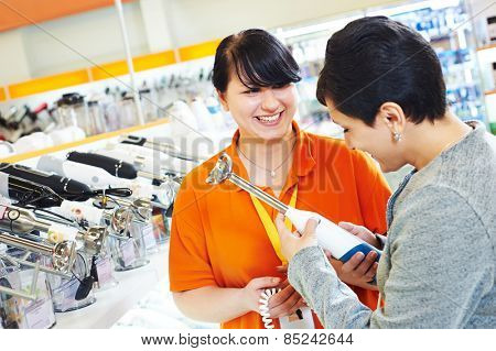 Young woman choosing electric blender in home appliance shopping mall supermarket