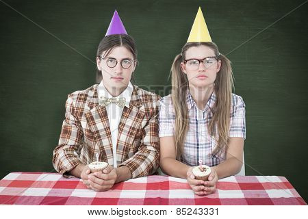 Unsmiling geeky hipsters celebrating birthday against green chalkboard