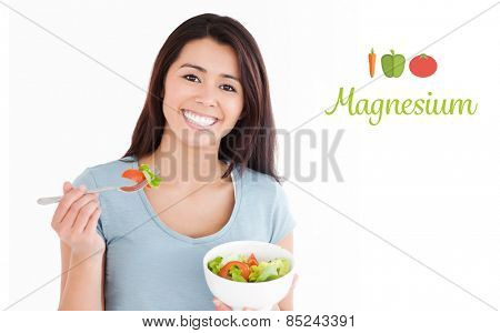 The word magnesium against beautiful woman eating a bowl of salad