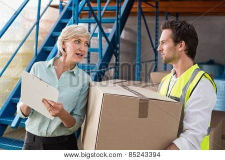 Warehouse manager and worker talking together in a large warehouse