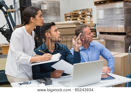 Warehouse manager pointing something to his colleagues in a large warehouse