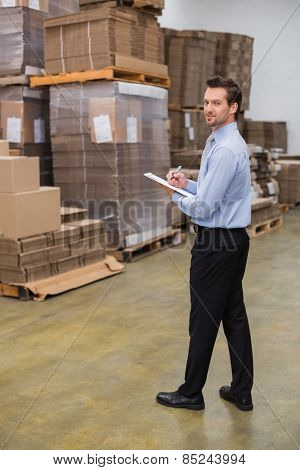 Warehouse manager looking at camera in a large warehouse