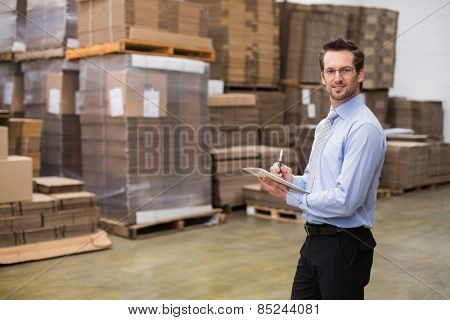 Manager looking at camera while holding clipboard in a large warehouse