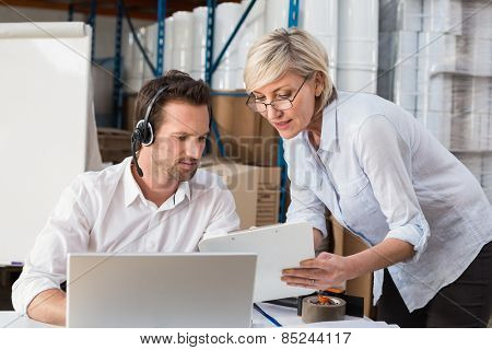 Warehouse manager showing something to her colleague in a large warehouse