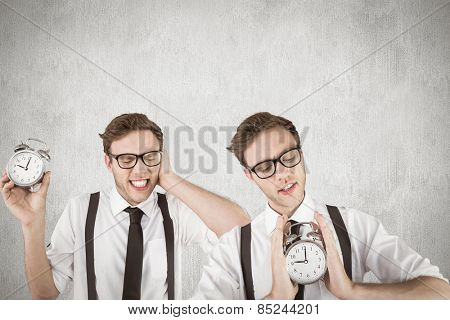 Nerdy businessman with alarm clock against white and grey background