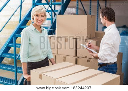 Focused warehouse managers with clipboard in a large warehouse