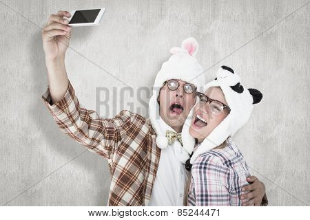 Geeky hipster couple taking selfie with smart phone against white background