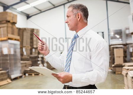 Warehouse boss checking his inventory in a large warehouse