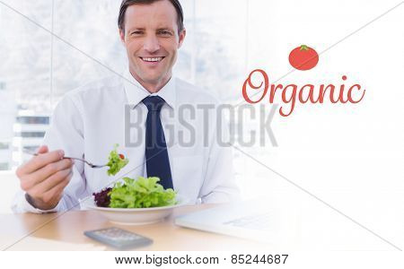 The word organic against happy businessman eating a salad on his desk