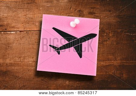 Airplane against pink adhesive note with pushpin