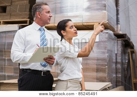 Warehouse manager and her boss checking inventory in a large warehouse