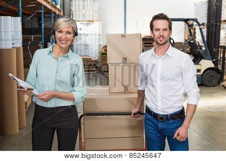 Manager walking with her colleague pulling trolleys in a large warehouse