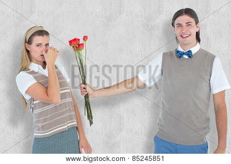 Geeky hipster offering red roses to his girlfriend against white background