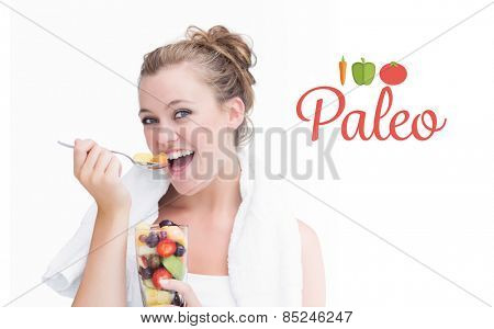 The word paleo against woman eating fruit and smiling
