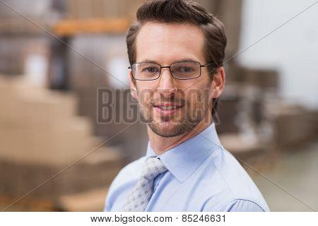 Smiling warehouse manager wearing eyeglasses in warehouse