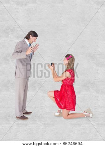 Pretty hipster on bended knee doing a marriage proposal to her boyfriend against white background