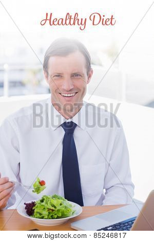 The word healthy diet against cheerful businessman eating a salad on his desk