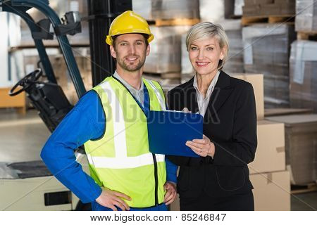 Forklift driver and his manager smiling at camera in a large warehouse