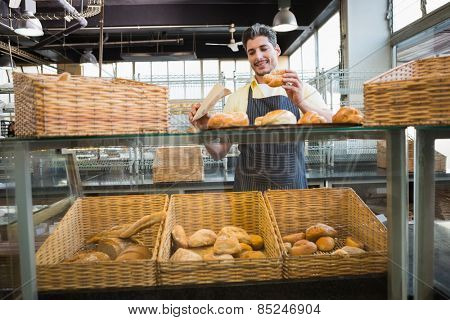 Smiling waiter in apron choosing bread at the bakery