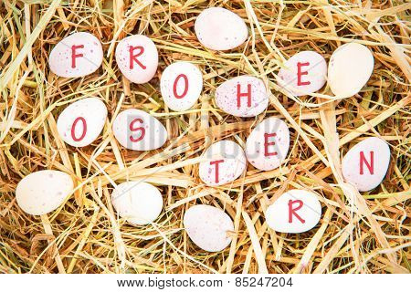 frohe ostern against little candy easter eggs on straw