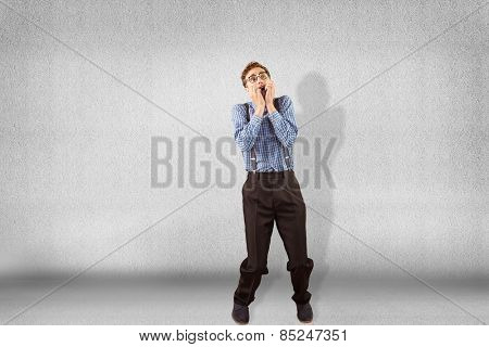 Geeky hipster biting his nails against grey wall