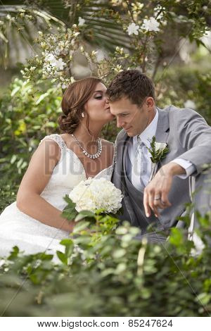 Newly married couple having intimate moment together in garden