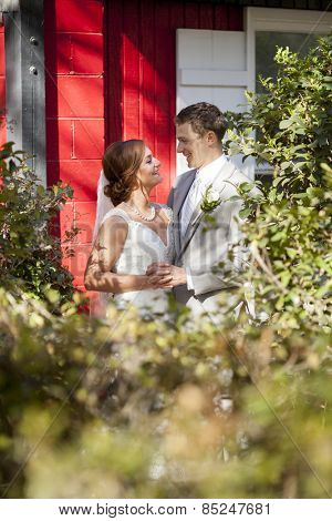Newly married couple together in the garden in sunlight