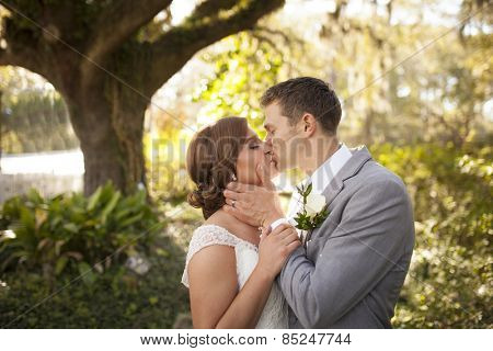 Newly married couple in intimate embrace in garden