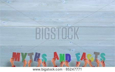 Hands holding up myths and facts against bleached wooden planks background