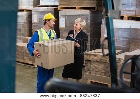Warehouse worker and his manager working together in a large warehouse