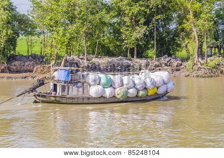 CHAU DOC, VIETNAM - JANUARY 2, 2013: Rural life in Mekong delta -Barge transports marchandise on Bassac River