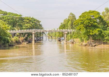 CHAU DOC, VIETNAM - JANUARY 2, 2013: Rural life in Mekong delta -Bridge over one of canals and fishing boats mooring at the riverside of Bassac River