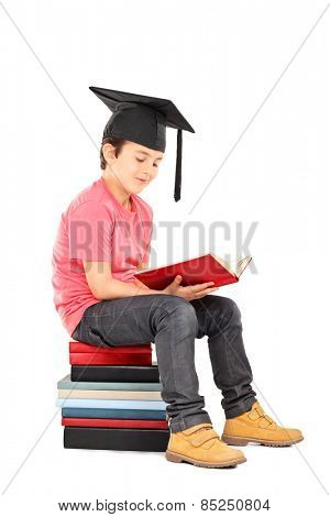 Kid with mortarboard reading a book seated on a stack of books isolated on white background