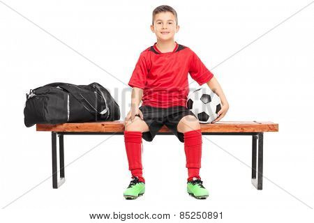 Junior soccer player sitting on a bench and holding a football isolated on white background