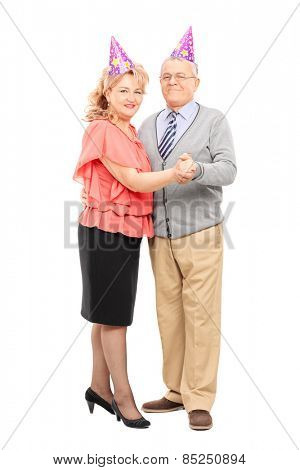 Full length portrait of a mature couple dancing at some party isolated on white background