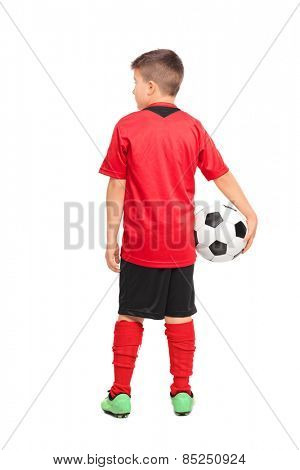 Full length portrait of a junior soccer player holding a ball isolated on white background, rear view
