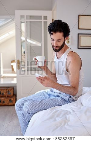man with mobile cellphone and coffee sitting on bed at home