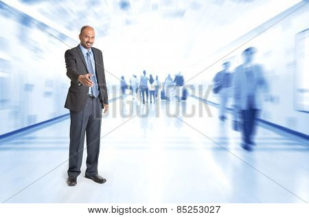 Full body Indian businessman offering hand shake at corridor, inside business building with motion blurred people as background.