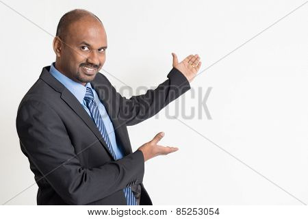 Indian businessman hands showing something on copy space, standing on plain background.